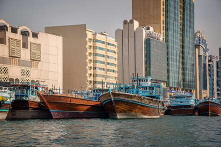 Wooden dhow cargo boats in Dubai Creek, modern buildings in the background, United Arab Emirates