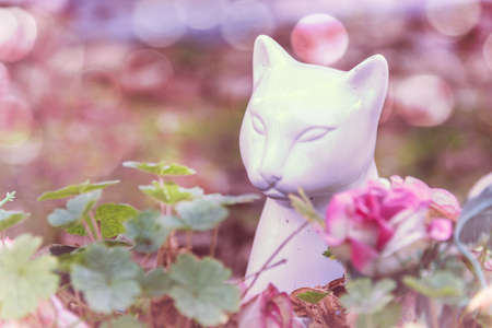 White ceramic cat statue in the pet cemetery of Paris in Asnières-sur-Seine, France. The Cemetery of dogs and other domestic animals is the oldest pet cemetery in the world.