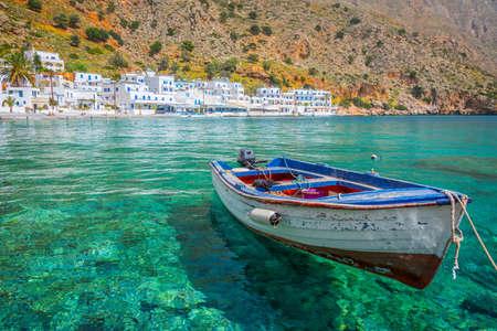 Fishing boat and the scenic village of Loutro in Crete, Greece Banco de Imagens