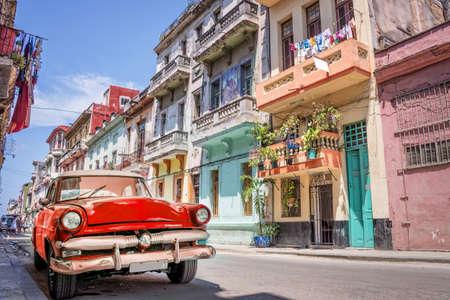 Vintage clásico coche americano rojo en una colorida calle de La Habana, Cuba.