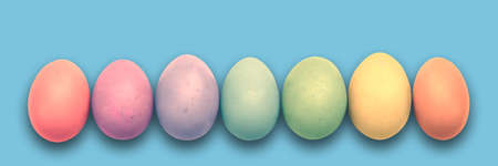Pastel painted Easter eggs aligned in a row on blue panoramic background, Easter web banner Banco de Imagens