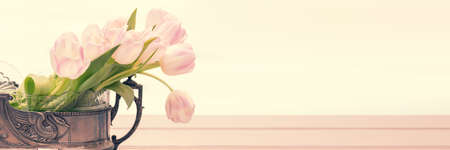 Still life with pink tulip bouquet in a vintage vase on panoramic background with copy space