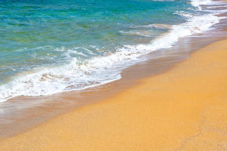 Waves on a beach with orange sand and blue water Banco de Imagens