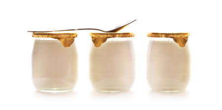 Three plain yogurts in glass jars and a spoon isolated on white background Banco de Imagens