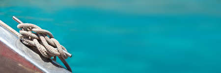 Close up of a rope on a sailboat, sea in the background, panoramic web banner