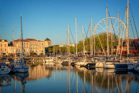 Colorful sailboats at sunset in the old harbor of La Rochelle, France