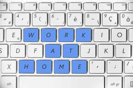 Work at home written on a computer keyboard background Stock Photo