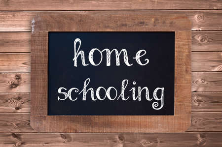 Homeschooling written on a vintage blackboard with wooden frame Stock Photo