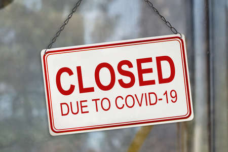 Closed sign due to Covid-19, Coronavirus outbreak lockdown, on the window of a shop. Economic crisis concept