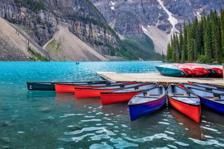 Corlorful canoes on Moraine lake near Lake Louise village in Banff National Park, Alberta, Rocky Mountains, Canada Editorial