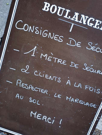 Social distancing rules for shopping written in French on a blackboard in a bakery