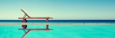 Reclining chair near a swimming pool, travel panoramic background with copy-space Stock Photo