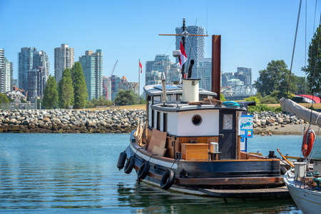 Old wooden boat in Vancouver heritage harbour, Vancouver skylin in the background, British Columbia, Canada