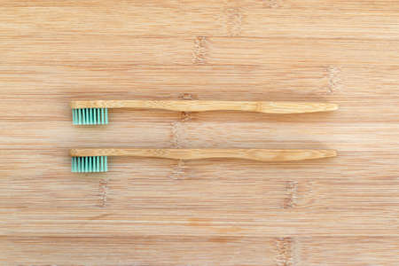 Set of two bamboo toothbrushes on wood background. Zero waste, biodegradable material, environment concept