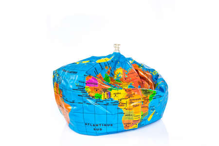 Planet earth toy balloon deflated isolated on white background. Earth overshoot day, unsustainable resources consumption concept Stock Photo