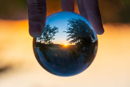 Rural landscape with trees at sunset seen through a crystal ball