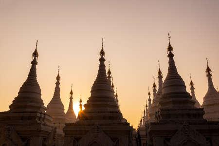 White stupas of Sanda Muni Pagoda at sunset in Mandalay, Burma Myanmar