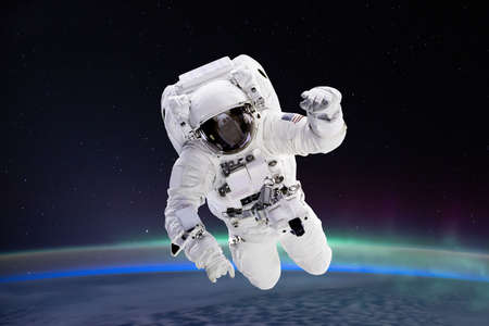 Composite image of astronaut floating in space, earth planet in the background Stockfoto