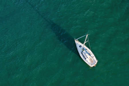 Aerial drone view of a sailing boat on emerald water