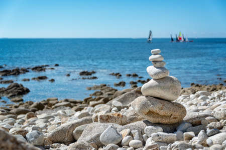 Pile of stones on a beach, ocean background in Brittany, France