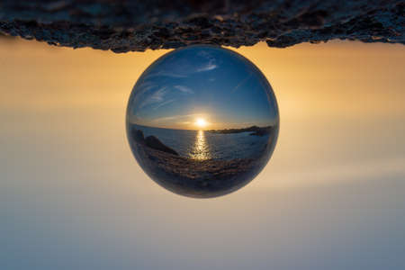 Sunset at the ocean seen through a crystal ball