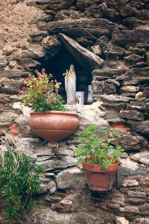 Virgin Mary statue in a wall in the village of Vescovato, Corsica, France