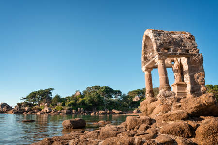 Statue of Saint Guirec on the beach of Ploumanach in Perros-Guirec, Côtes d'Armor, Brittany, France Stock Photo