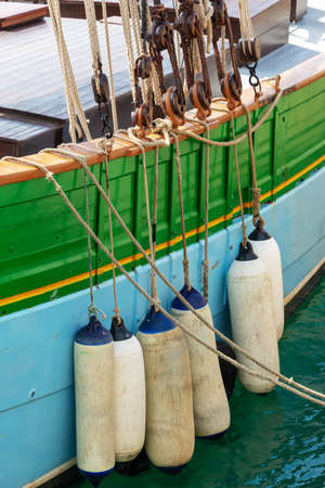 Buoys hanging outside the hull of an ancient colorfull wooden sailing boat Stock Photo