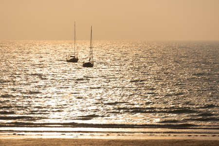 Silhouette of sailing boats at sunset on a beach in Pléneuf, Côtes d'Armor, Britanny, France