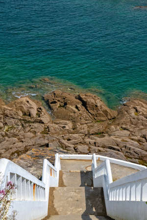 White stairs going down to rocks and blue sea. Vertical ocean background
