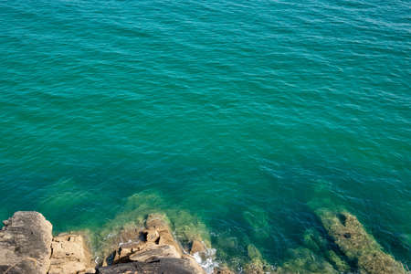 Looking down to rocks and blue pristine sea. Ocean background with copy space