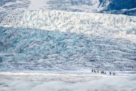 Line of tourists walking on Athabasca glacier in Columbia Icefield, Jasper National park, Rocky Mountains, Alberta, Canada Stock Photo