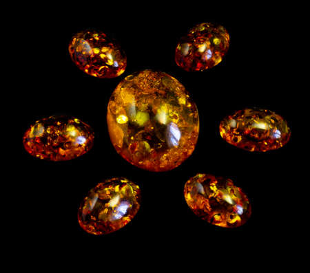 Cabochons of fake amber on a black background