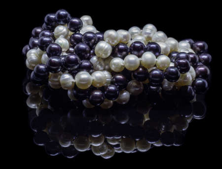 Two mixed strands of natural black pearl beads on a black background