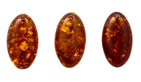 Natural three cabochons of glossy manmade amber close up 스톡 콘텐츠 - 129106302