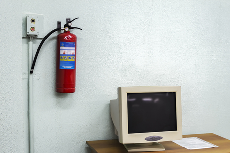 old computer and a fire extinguisher on the wall in the classroom