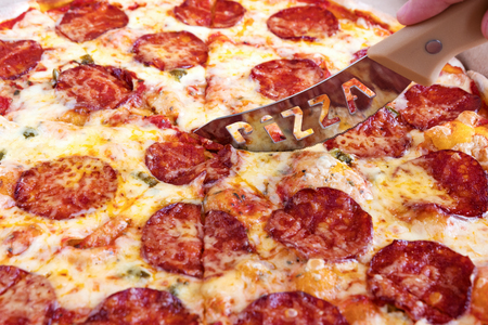 Pizza Pepperoni. Cut a slice of pizza with a knife. Close up Stock Photo