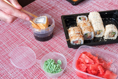 Sushi roll set, soy sauce, wasabi, chopsticks in a disposable container on a napkin. Hand lowers the roll in soy sauce