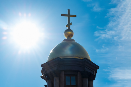 Gold dome and a cross on a background of blue sky and bright sunlight.