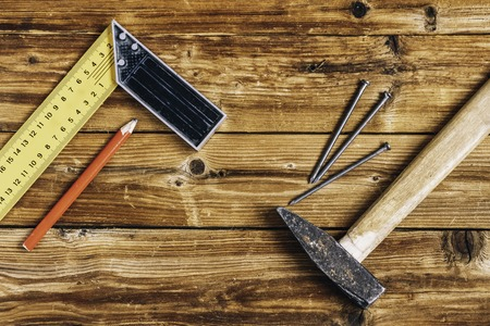 Nails, old hammer, pencil and measuring angle on wooden background Stock fotó