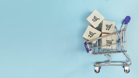 Boxes in a shopping cart on blue background. Concept: online shopping, e commerce and delivery of goods. Copy space