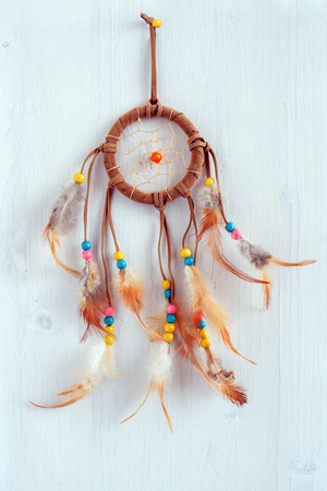 Dreamcatcher, american native amulet on wooden background. Shaman symbol