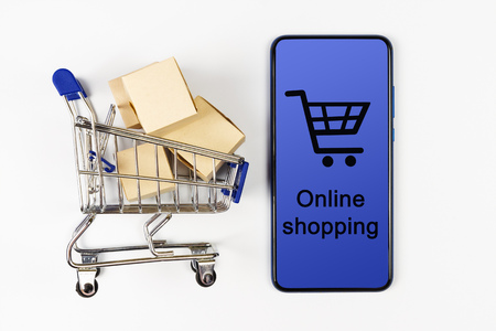 Supermarket cart with boxes and smartphone on white background. Online shopping Stockfoto