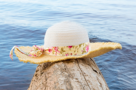 Womens hat with wide brim on a log on the water