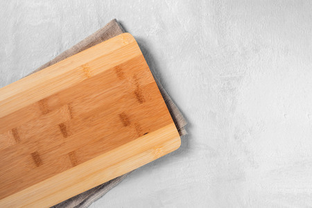 Kitchen cutting Board made of bamboo and napkin on the table. Copy space