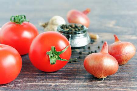 Tomatoes, onions, garlic and black pepper on wooden background