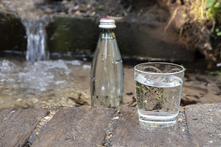 Natural ecological spring water. Glass bottle and glass of cold water stands in nature