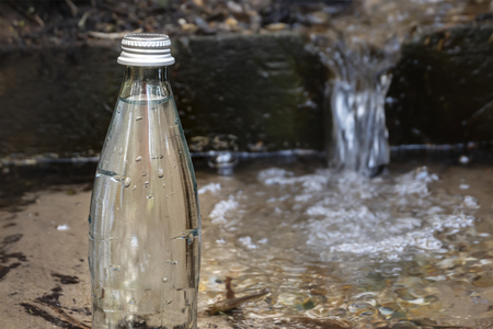 Natural ecological spring water. Glass bottle with cold water stands in nature