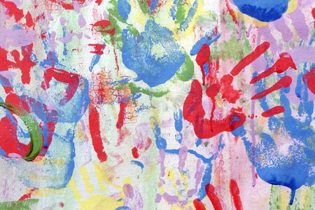 Color background of children's handprints. Multi colored hand prints.
