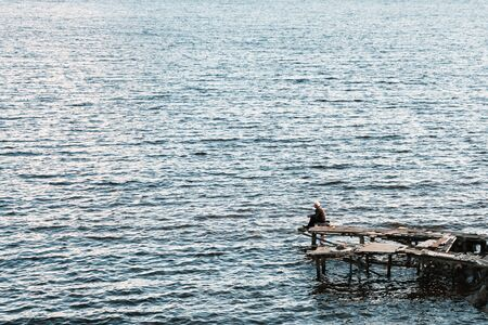 A lonely man sitting on a wooden bridge on the shore 写真素材